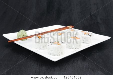 Japanese Cuisine - California Roll with Cucumber , Cream Cheese and Raw Salmon inside. Served with wasabi . over black table . on square white plate
