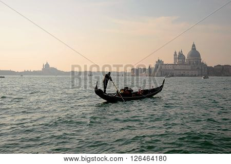 Traditional Gondola on Canal Grande with San Giorgio Maggiore church in the background in at sunset San Marco, Venice, Italy.
