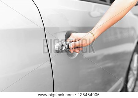 Hand woman pushing button of car handle to open car
