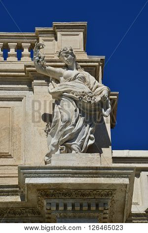 Allegorical marble statue symbolizing the joy of prairies and gardens from the attic of the wonderful Trevi Fountain in the center of Rome (18th century)