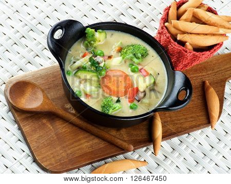 Delicious Homemade Vegetables Creamy Soup with Broccoli Carrots Zucchini Leek Red Bell Pepper and Green Pea in Black Iron Stewpot with Wooden Spoon and Bread Sticks closeup Wicker background