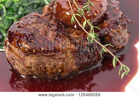 Delicious grilled fillet mignon steak with chard covered with red wine sauce. Macro. Selective focus on the steak. Photo can be used as a whole background.