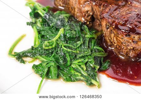 Delicious grilled fillet mignon steak with chard covered with red wine sauce. Macro. Selective focus on heap of chard. Photo can be used as a whole background.