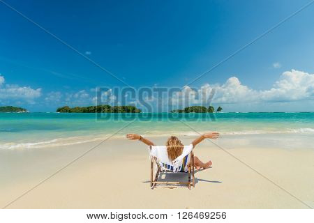 Woman on a lounge chair at the  tropical beach with hat