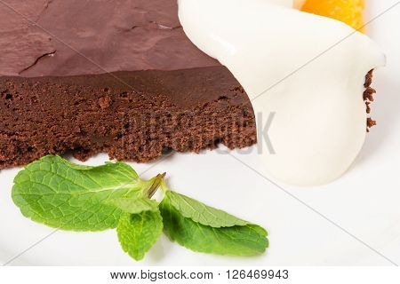 Chocolate cake with ice cream scoop on a sliced orange and mascarpone. Macro. Photo can be used as a whole background.