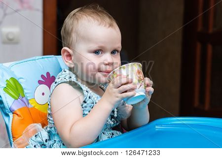 little girl in a smart dress sitting in a chair for feeding and drinking from a cup