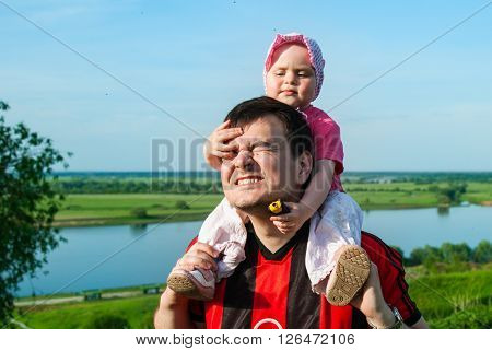 Father carries a child on his shoulders against the backdrop of a beautiful landscape with the river fields and sky