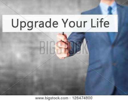 Upgrade Your Life - Businessman Hand Holding Sign