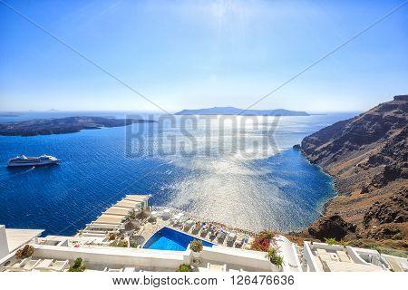 Santorini, Greece - July 04, 2013: Beautiful typical white greek buildings with swimming pool. Sea side of Thira, Santorini island