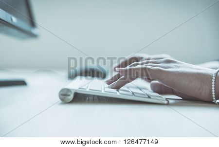 Woman hands typing on computer keyboard close up