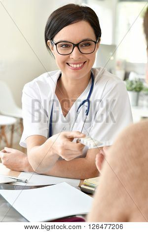 Doctor giving drugs to patient in office
