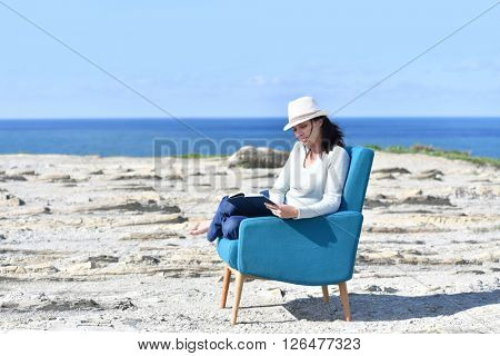 Woman reading book in armchair by the sea