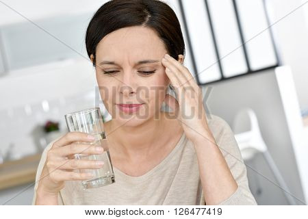 Mature woman having migraine, drinking water