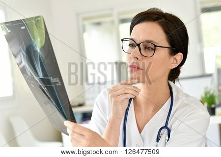 Doctor reading Xray results in office