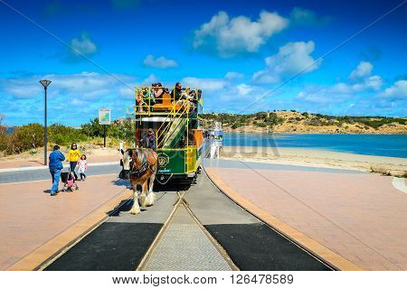 Adelaide Australia - November 16 2013: The Victor Harbor Horse Drawn Tram with people on board arriving from the Granite Island on a day