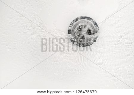 White bathroom sink drain close up with water ripple and bubbles