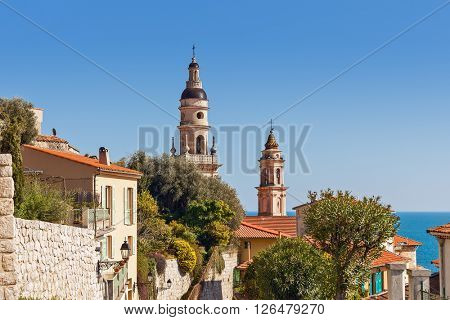 Two campaniles among houses under blue sky as Mediterranean sea on background in Menton, France.