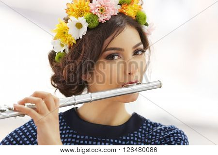 Beautiful young woman with flute on window background