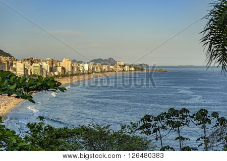 Panoramic image of Ipanema Leblon and Arpoador beaches seen during the sunset of Rio de Janeiro through the vegetation