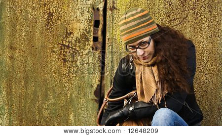 beautiful young adult woman in a cap and glasses against a grungy rusty wall