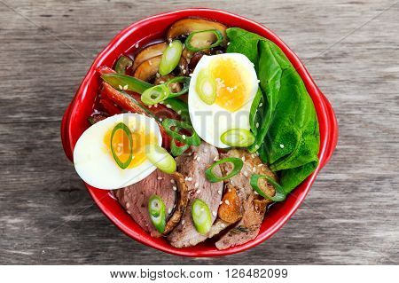 Duck noodles with egg, vegetables and duck meat in bowl.