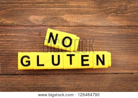 Phrase NO GLUTEN made of yellow cubes on wooden background