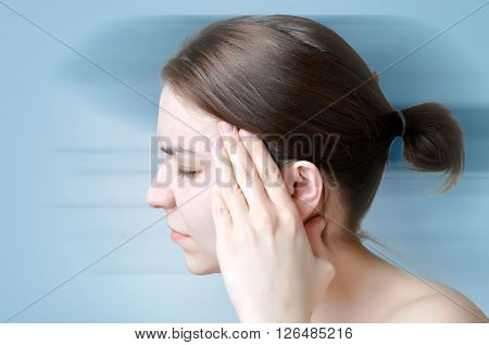 A young woman touching her painful head