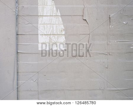 Detail of a grey wall painted over rests of paper
