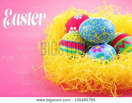 Easter greeting card. Multicoloured eggs in straw on pink background