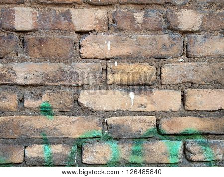 Detail of a pbricks wall with green paint on it