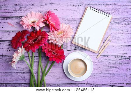Gerbers and cup of coffee on wooden purple background
