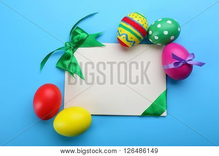 Easter eggs with greeting card on blue background