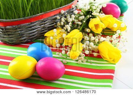 Multicoloured Easter eggs and tulips on napkin, closeup