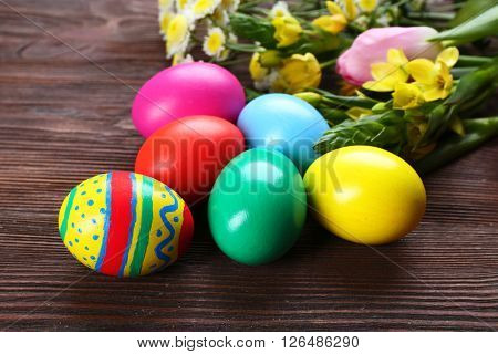 Easter eggs with spring flowers on wooden background