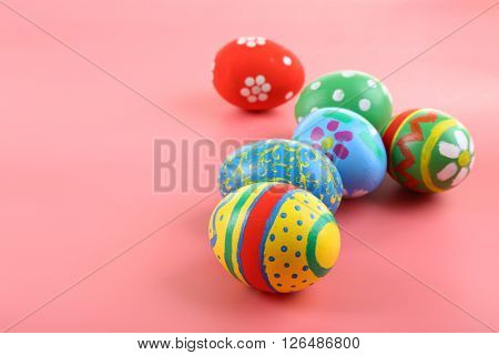 Multicoloured Easter eggs on pink background
