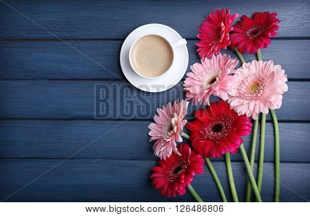 Fresg gerbers and cup of coffee on wooden background