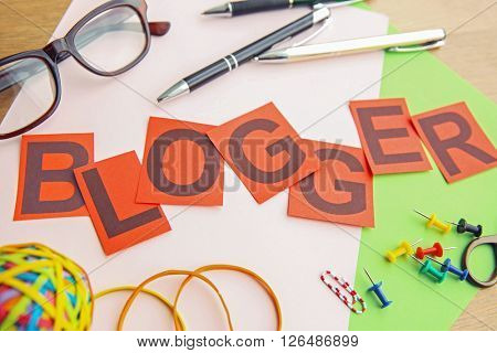 Internet blog concept. Word Blogger with stationery.