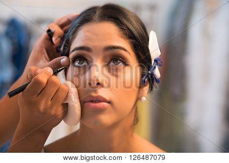 Close-up image of artist applying black eyeliner to lower lash line