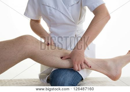 Physiotherapist Controlling Leg Of A Patient In Bright Office