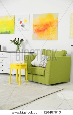Modern living room interior with green chair, yellow coffee table and bright canvases on the white wall