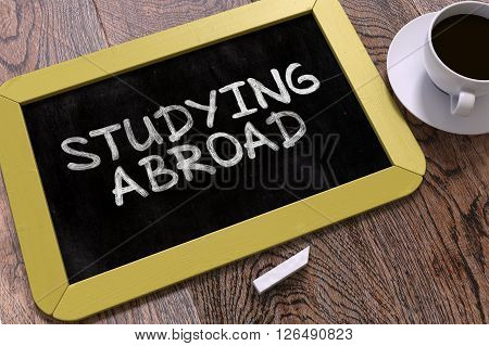 Studying Abroad - Yellow Chalkboard with Hand Drawn Text and White Cup of Coffee on Wooden Table. Top View. 3D Render.