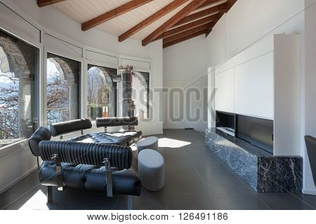Interior, living room of a villa, leather divan and fireplace