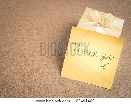 Hand writing - Thank you - words on yellow sticky note with gold gift box on wood background - vintage tone