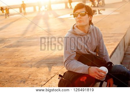 Young handsome traveller hipster man with backpack  on the street,urban street style,casual man