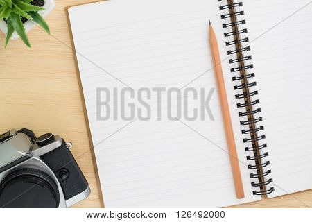 Open spiral notebook empty line paper with brown pencil and vintage camera and small plant - notebook paper on wood background - working desk top view