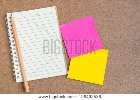 Top view of open spiral notebook empty line paper with brown pencil and colorful sticky notes - notebook paper on brown background