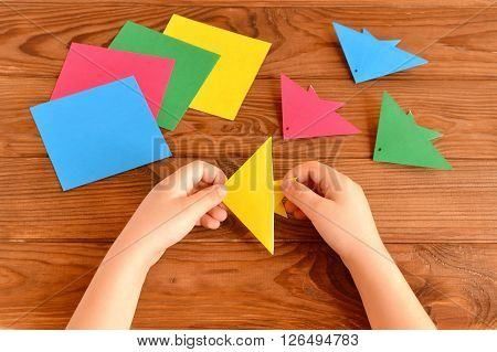 Origami colorful fish, paper sheets. Child holds an yellow origami fish in his hands. Brown wooden background