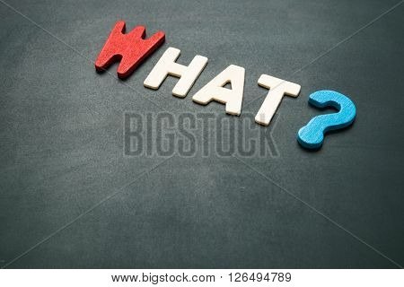 Text 'what' wording on blackboard - concept of 5 Ws questions - colorful alphabet made from wood