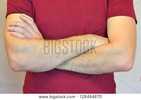 Male hands folded on his chest, concept