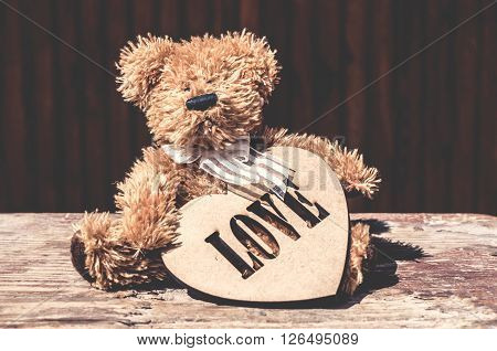 toy dog with a wooden heart on the table